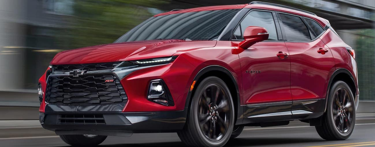 A red 2020 Chevy Blazer RS is driving past blurred buildings near Albany, NY.