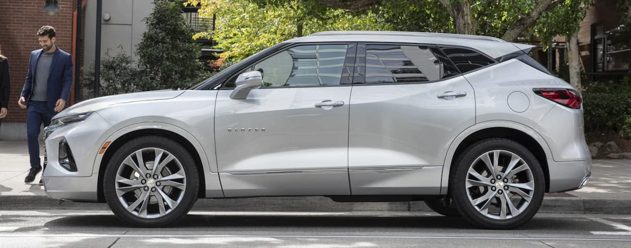 A side view of a silver 2020 Chevy Blazer is parked on the side of a treelined street.