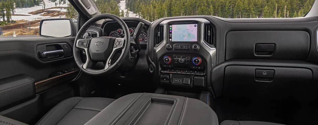 The front black leather interior of the 2020 Chevy Silverado 1500 is shown with an infotainment system and large drivers display.