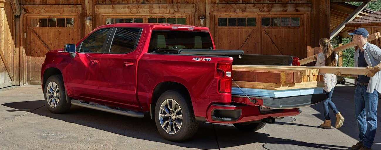 A couple is loading heavy pieces of wood into the bed of their red 2020 Chevy Silverado 1500.