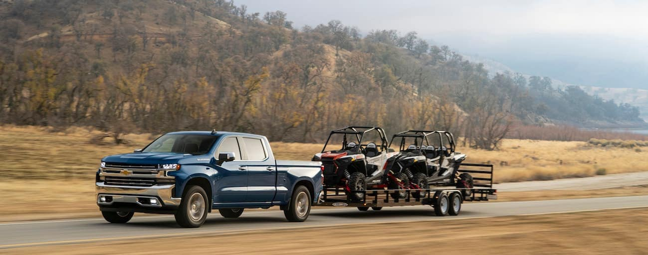 A blue 2020 Chevy Silverado 1500, which wins when comparing the 2020 Chevy Silverado 1500 vs 2020 Ram 1500, is towing a large trailer with two side by sides loaded on it.