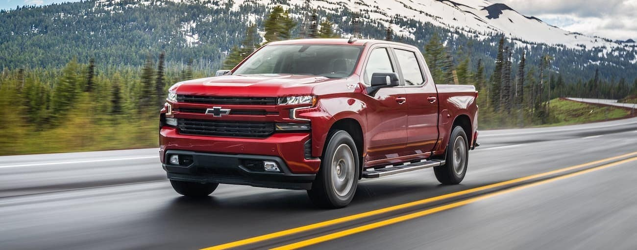 A red 2020 Chevy Silverado 1500 is driving on a highway with a mountain in the background.