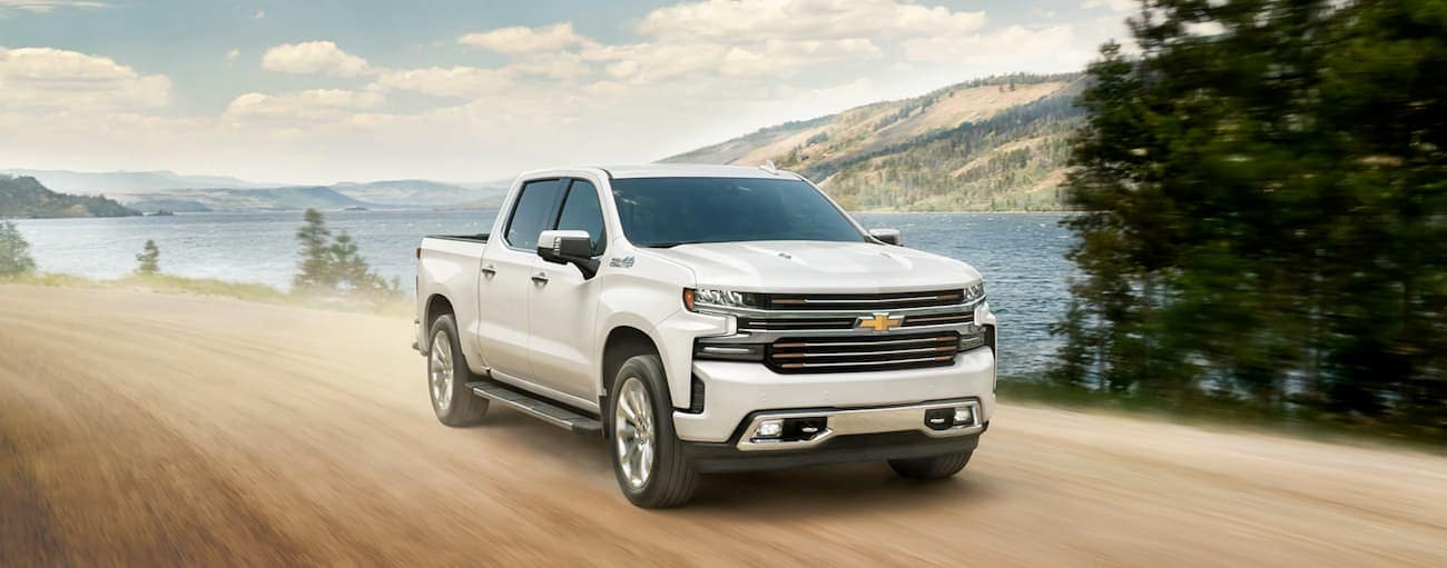 A white 2020 Chevy Silverado, which wins when compared to the 2020 Chevy Silverado 1500 vs 2020 Toyota Tundra, is driving on a dirt road in front of a lake.