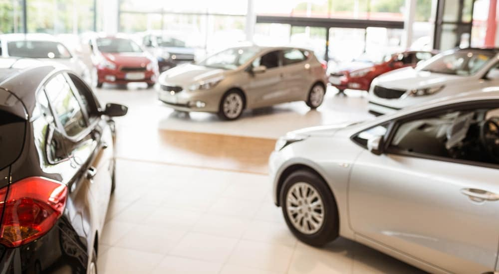 Cars are shown in a dealerships showroom.