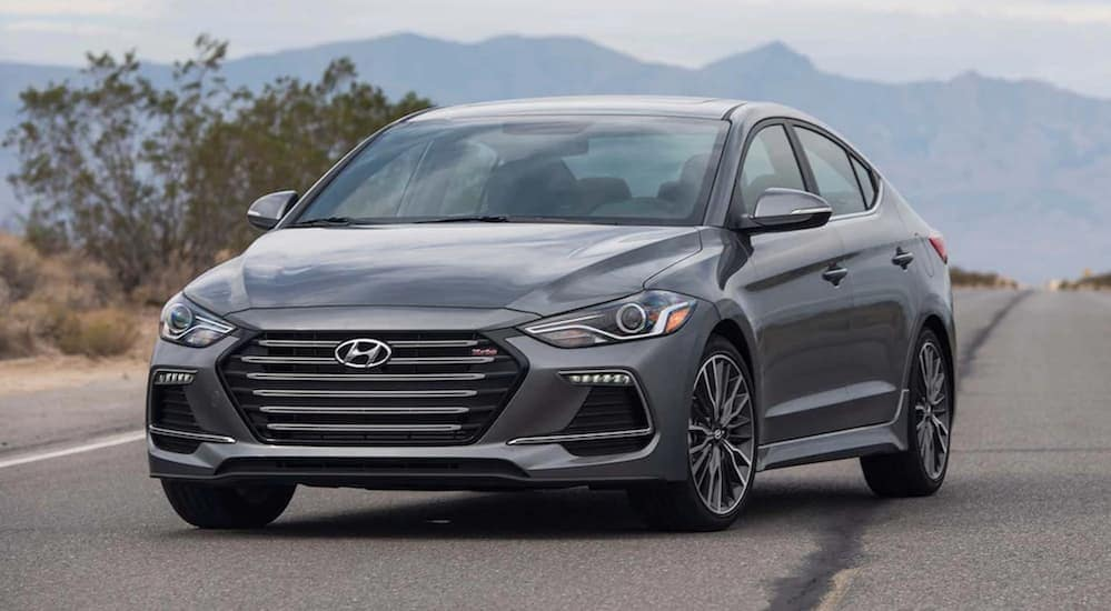 A grey 2017 Hyundai Elantra is parked on a road with mountains in the distance.