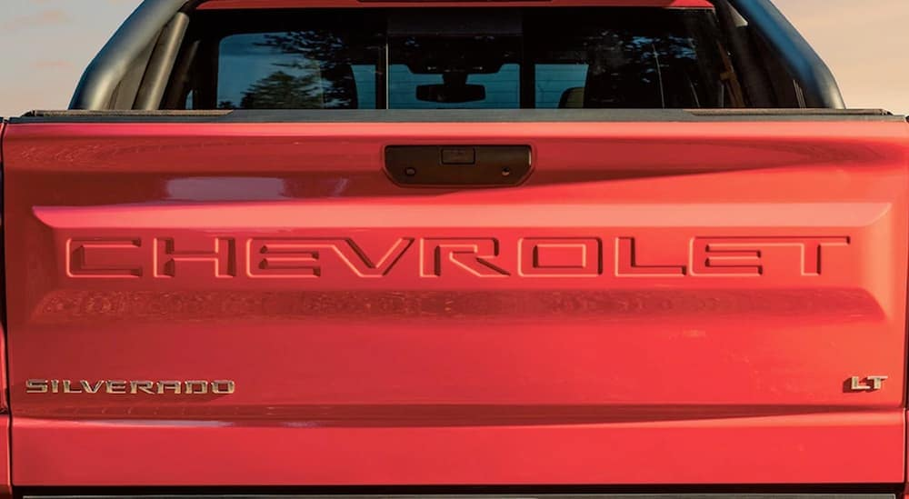 A close up of a red Chevy tailgate that says 'Chevrolet' on it.