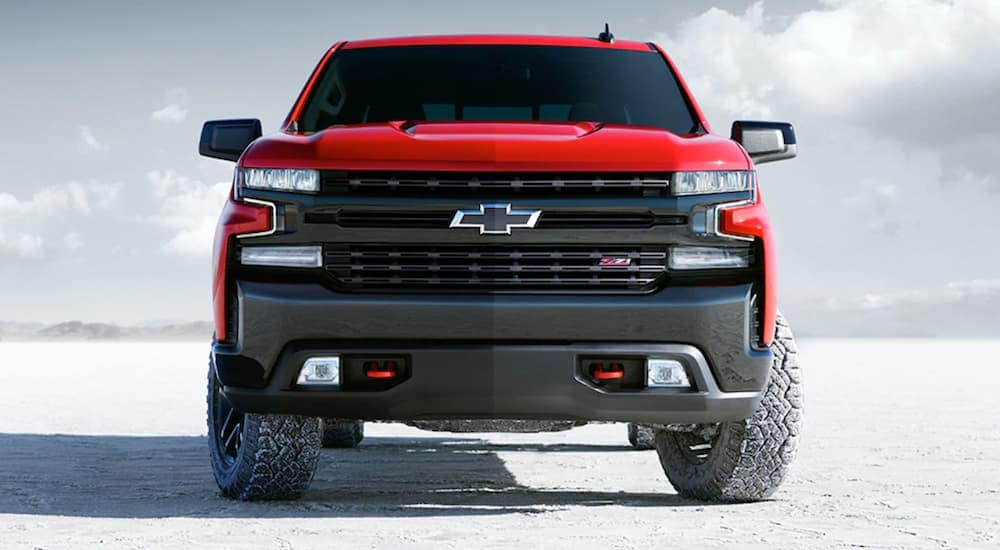 A red 2020 Chevy Silverado Trailboss, which is a popular option when you search Chevy dealer near me, is parked on a salt lot.