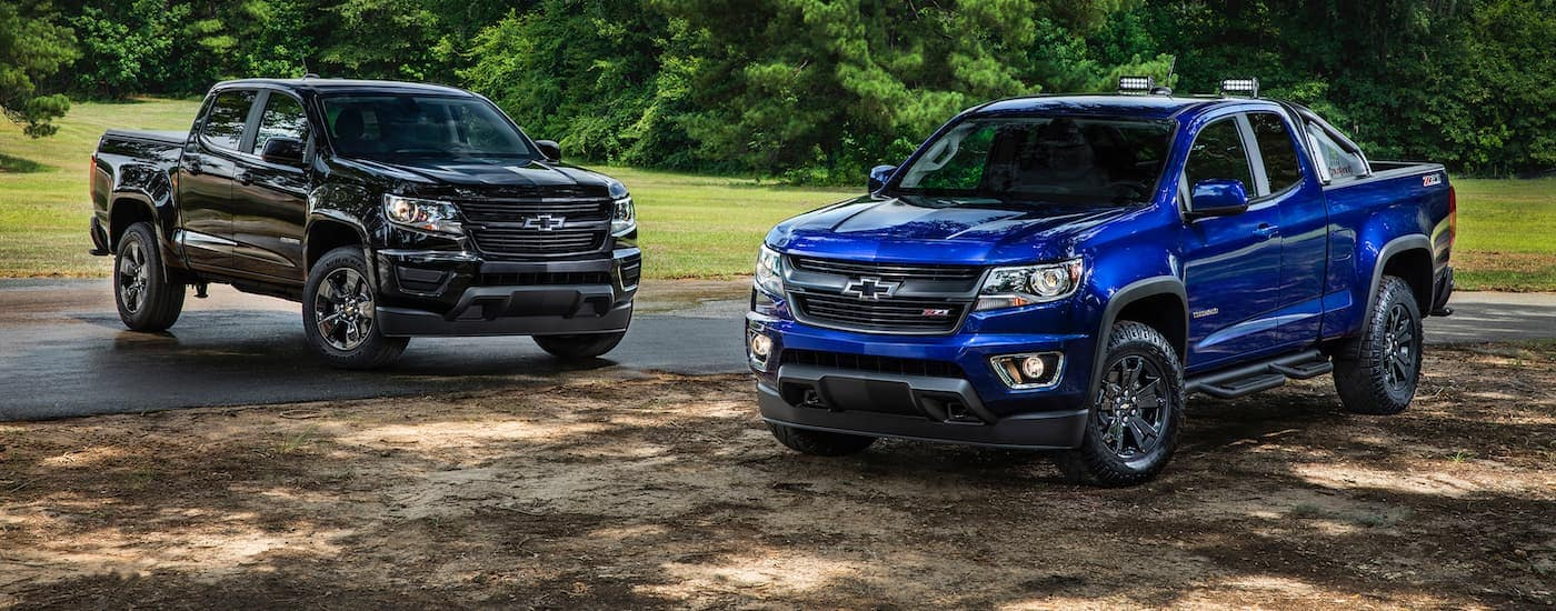 Two 2016 Chevy Colorados, in black and blue, are parked on a dirt path under trees.