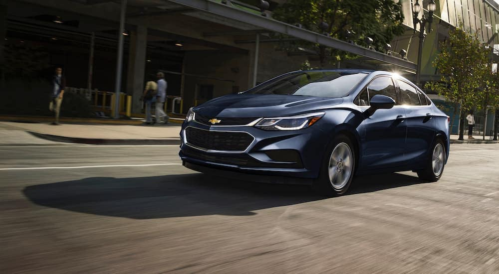 A blue 2017 Chevy Cruze, popular among used cars in Albany, NY, is driving downtown.