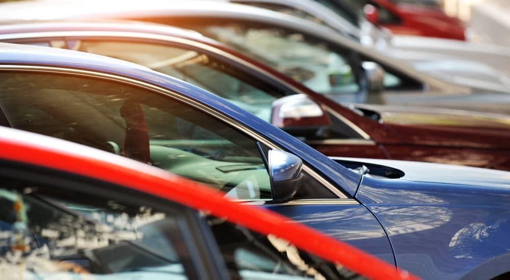 A row of used cars is shown at a used car lot.