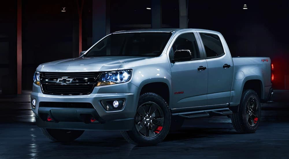 A silver 2020 Chevy Colorado Redline Edition is parked in a dark lit garage near Clifton Park, NY.
