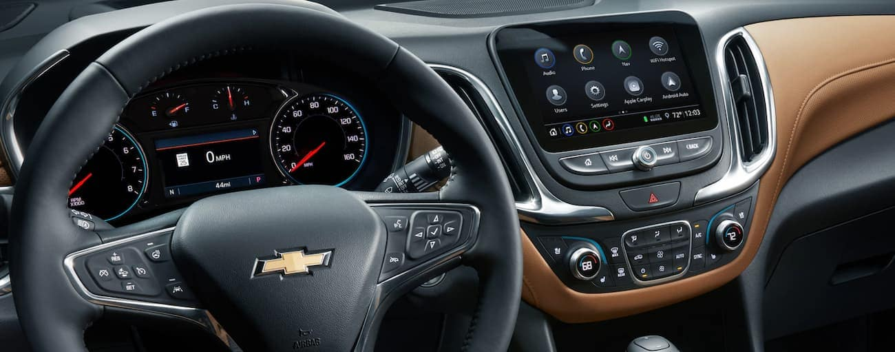 A close up of the black leather steering wheel and the infotainment system inside of a 2020 Chevy Equinox is shown.