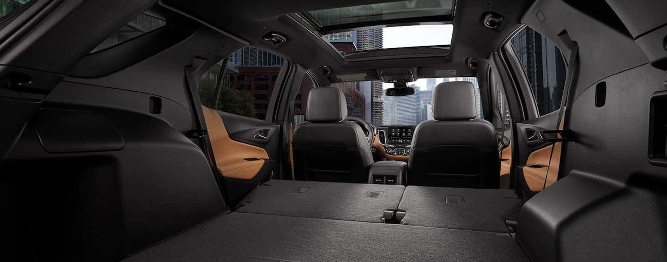 A rear to front view of the black interior of a 2020 Chevy Equinox is shown with the rear seats down.