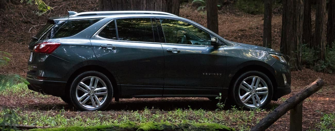 A side view of a blue 2020 Chevy Equinox, which wins when comparing the 2020 Chevy Equinox vs 2020 Toyota RAV4, is parked on a trail in the woods near Albany, NY.