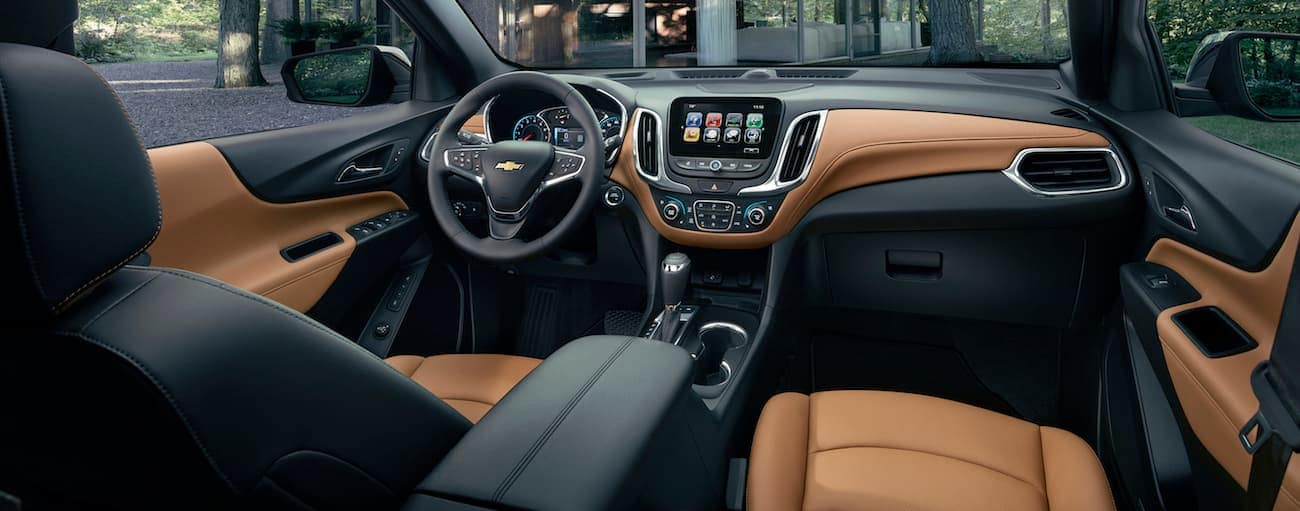 A front view of the black and brown leather interior inside of the 2020 Chevy Equinox is shown with an infotainment system.