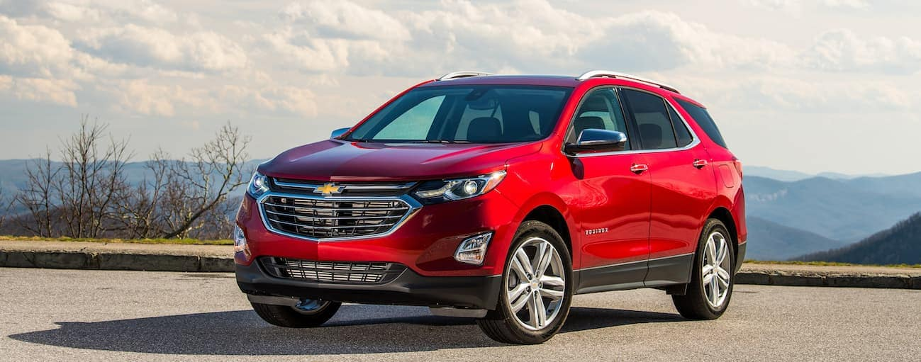 A red 2020 Chevy Equinox is parked in a dirt lot that's overlooking mountains.