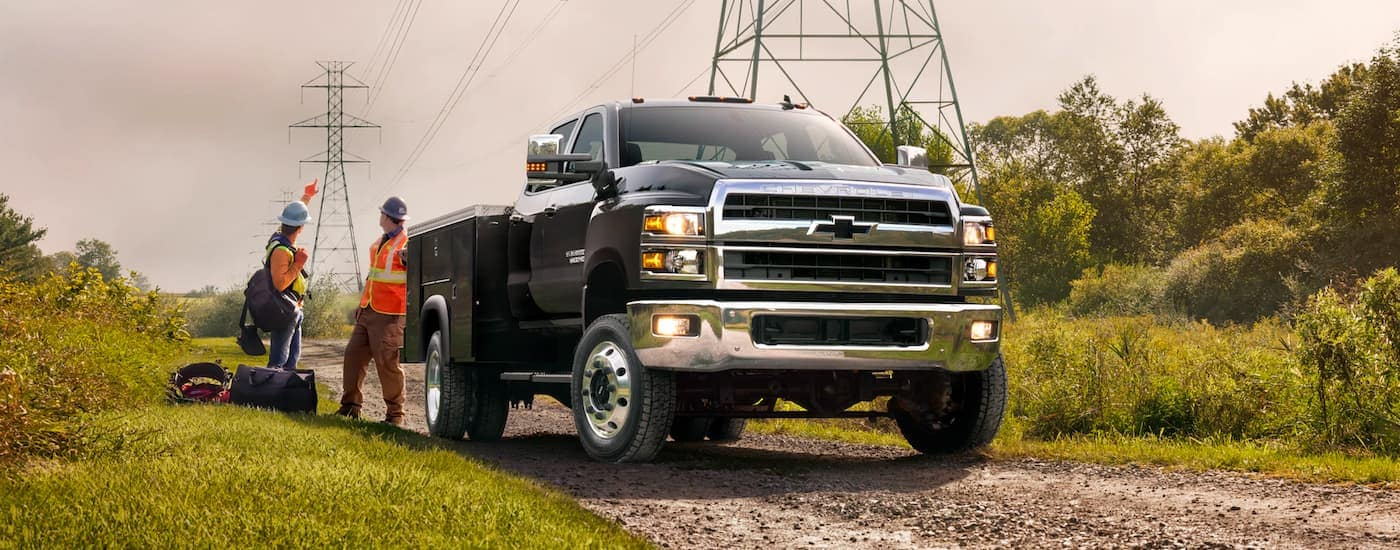 A black 2021 Chevy Silverado 5500 HD is shown parked under power lines with workers behinds it.
