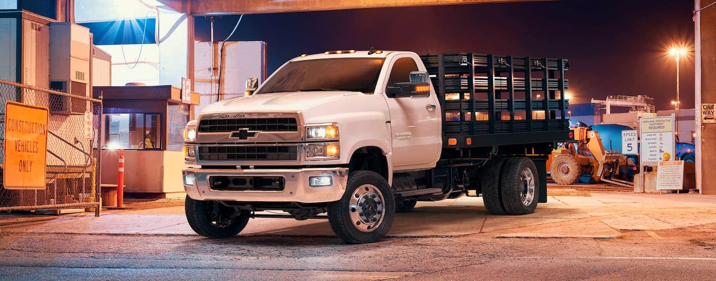 A white 2021 Chevy Silverado 5500 HD is shown from the front, angled left, in a shipping yard.