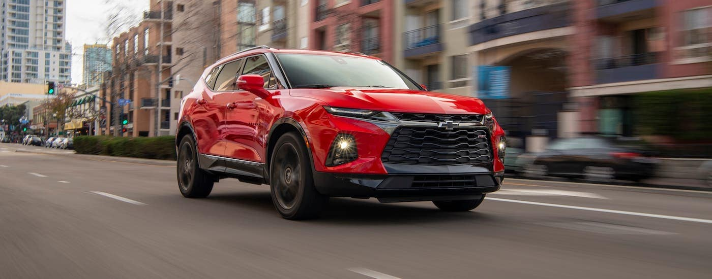 A red 2020 Chevy Blazer RS is driving on a downtown street near Clifton Park, NY.