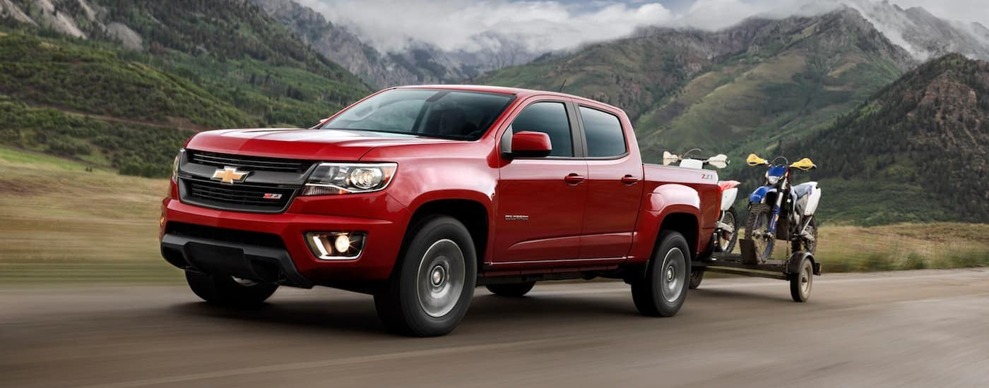 A red 2020 Chevy Colorado is towing a trailer with dirt bikes.