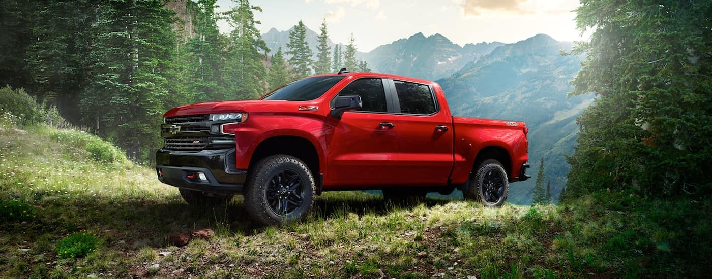 A red 2020 Chevy Silverado 1500 is off-roading near mountains.