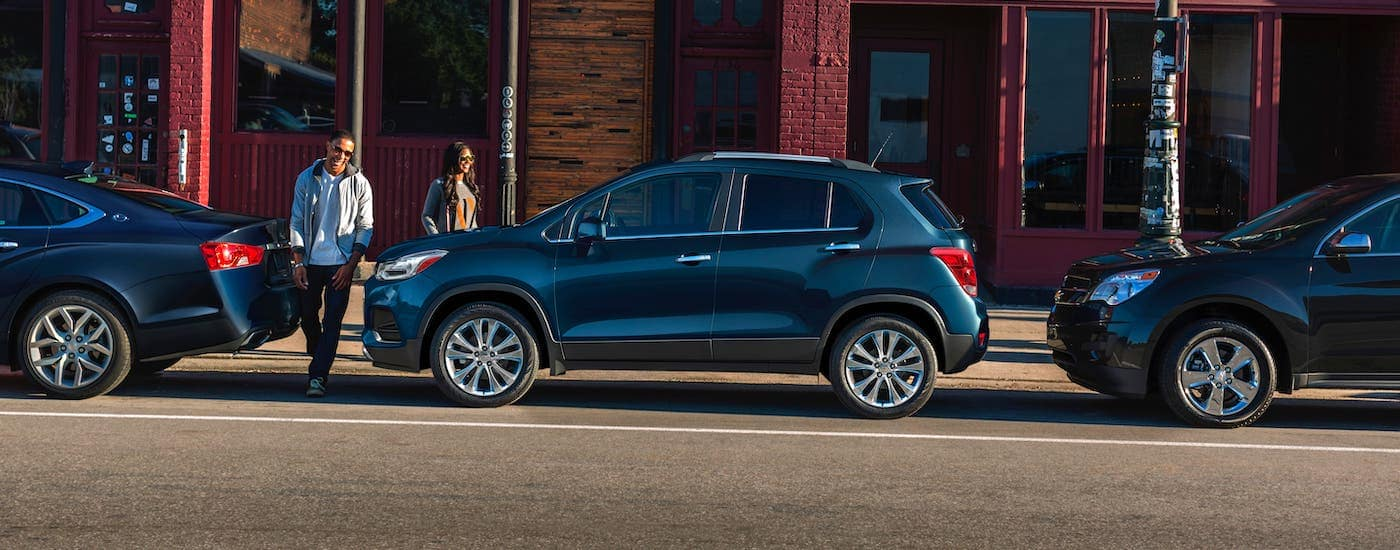 A couple is walking towards their blue 2020 Chevy Trax from a Chevy dealership near Clifton Park, NY.