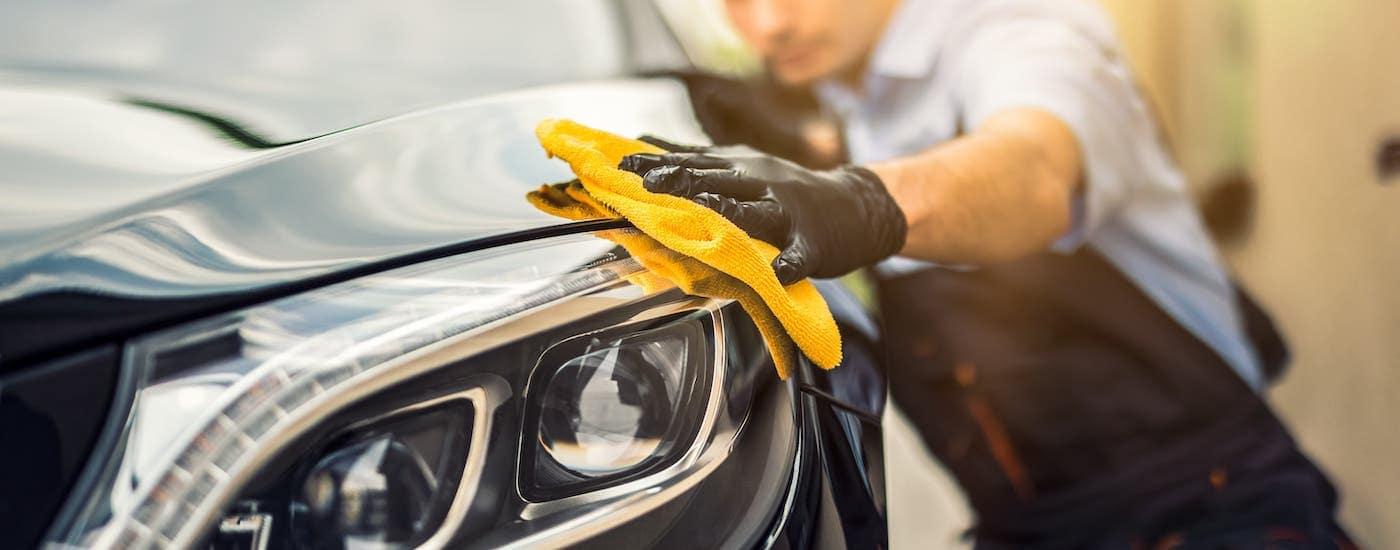 A car detailer is rubbing a cloth on a black car near Clifton Park, NY.