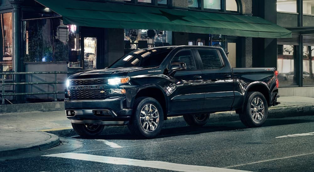 A black 2020 Chevy Silverado 1500 is parked in front of a store front after leaving a Chevy Dealership near Clifton Park, NY.