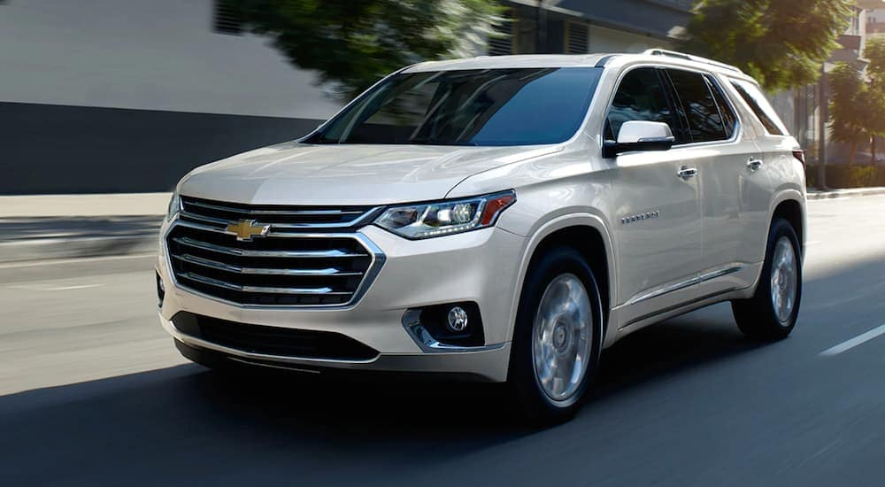A white 2020 Chevy Traverse is driving on a city street past blurred buildings.