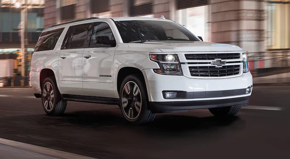 A white 2020 Chevy Suburban is driving on a city street after leaving a Chevy dealership in Clifton Park, NY.