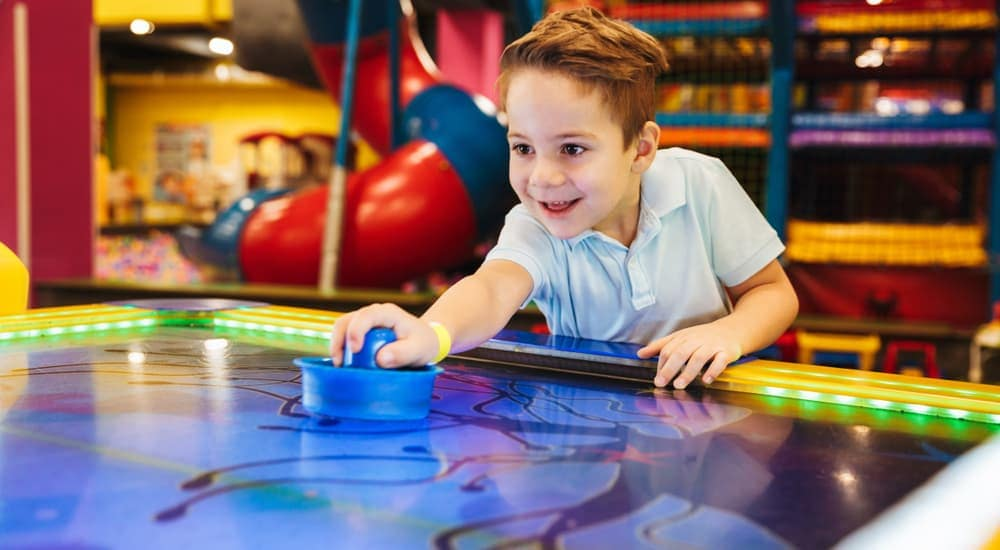 A smiling young boy is playing air hockey at a local Arcade Center.