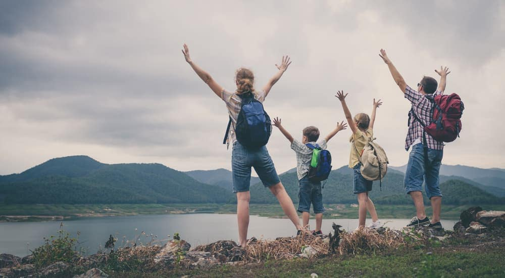 A family has their arms up in excitement while looking over a large lake after hiking near Clifton Park, NY.