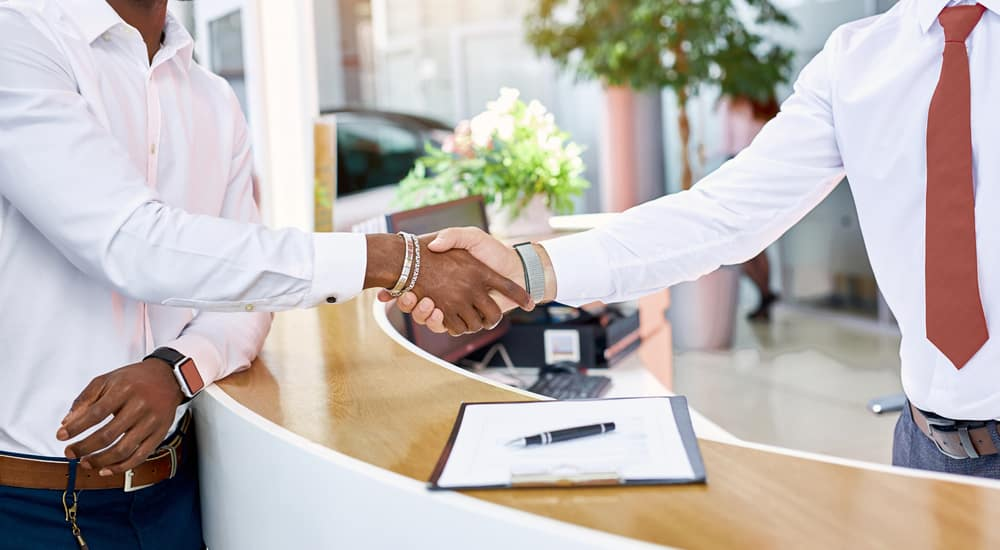 Two men in button-up shirts shaking hands over a counter and clipboard in a dealership showroom