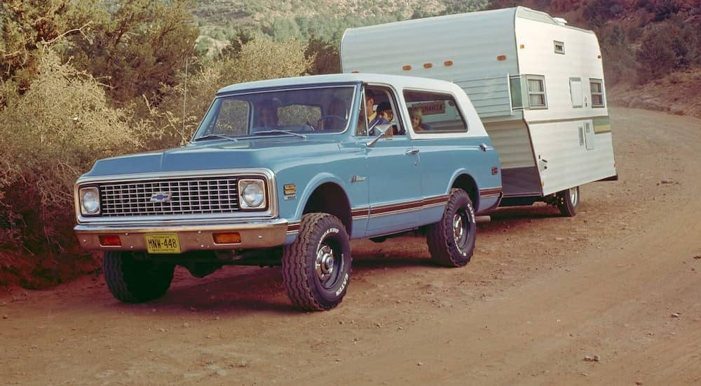 A blue 1969 Chevy K5 Blazer is towing a camper on a dirt trail near Albany, NY.