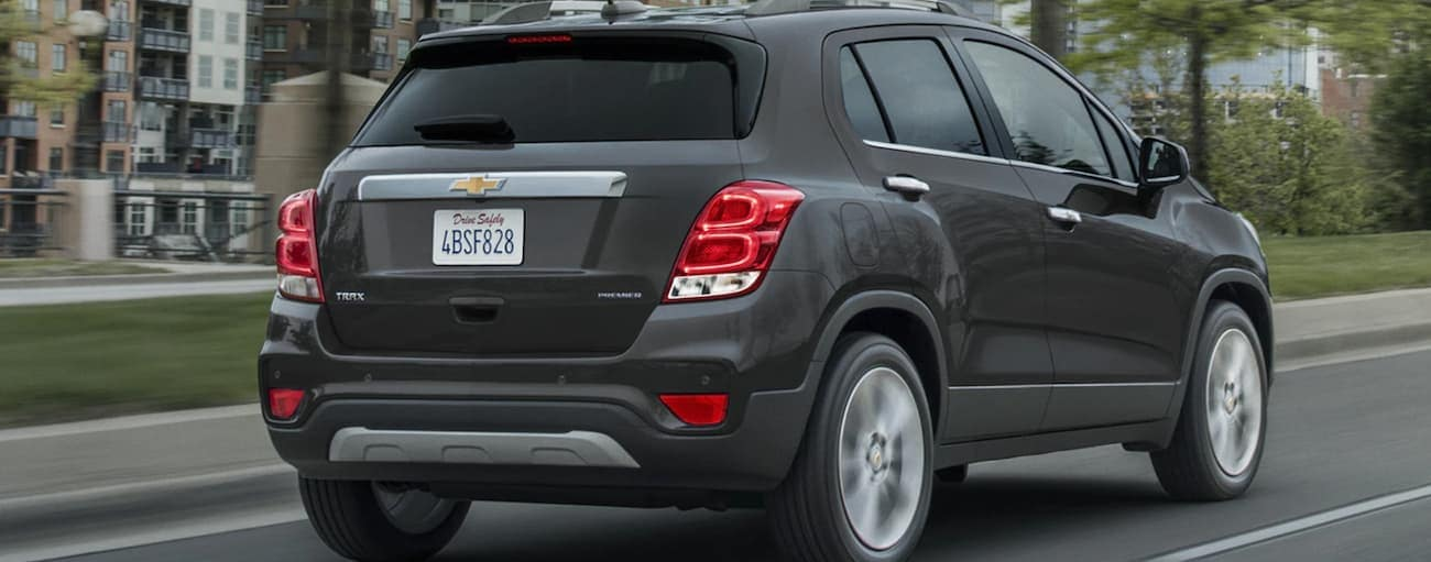 A dark grey 2020 Chevy Trax, which wins when comparing the 2020 Chevy Trax vs 2020 Buick Encore, is driving on a city street.