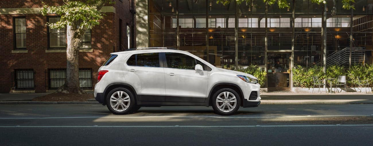A white 2020 Chevy Trax is shown on a city street in front of a cafe near Albany, NY.