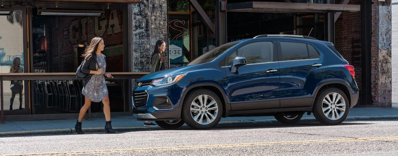 Two women are walking to a blue 2020 Chevy Trax on a downtown Albany, NY street.