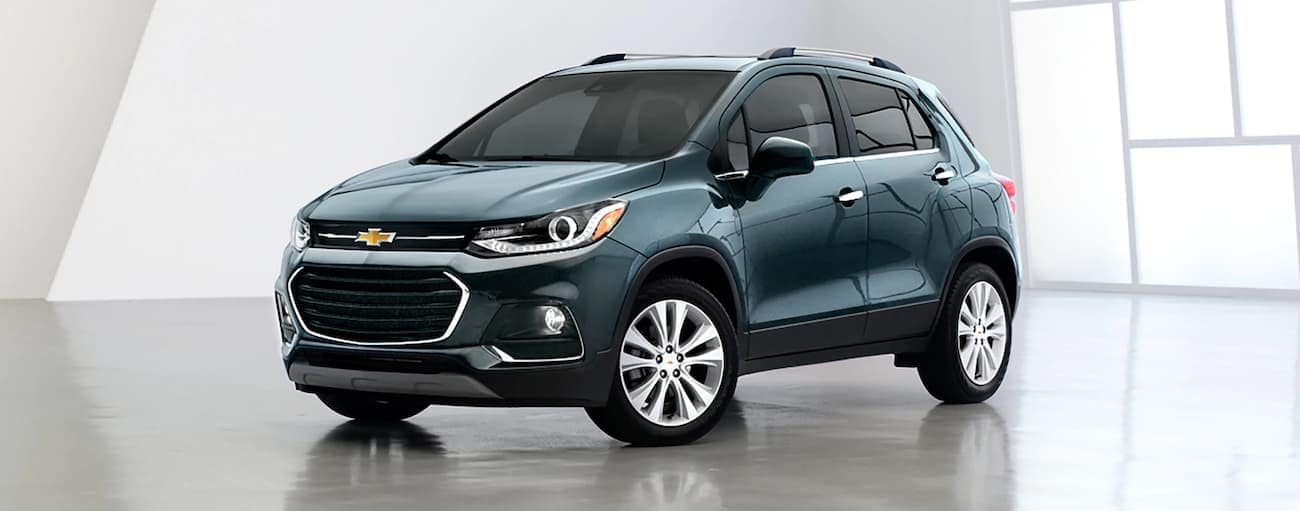 A teal 2020 Chevy Trax is shown in a white showroom and wins when comparing the 2020 Chevy Trax vs 2020 Ford EcoSport.
