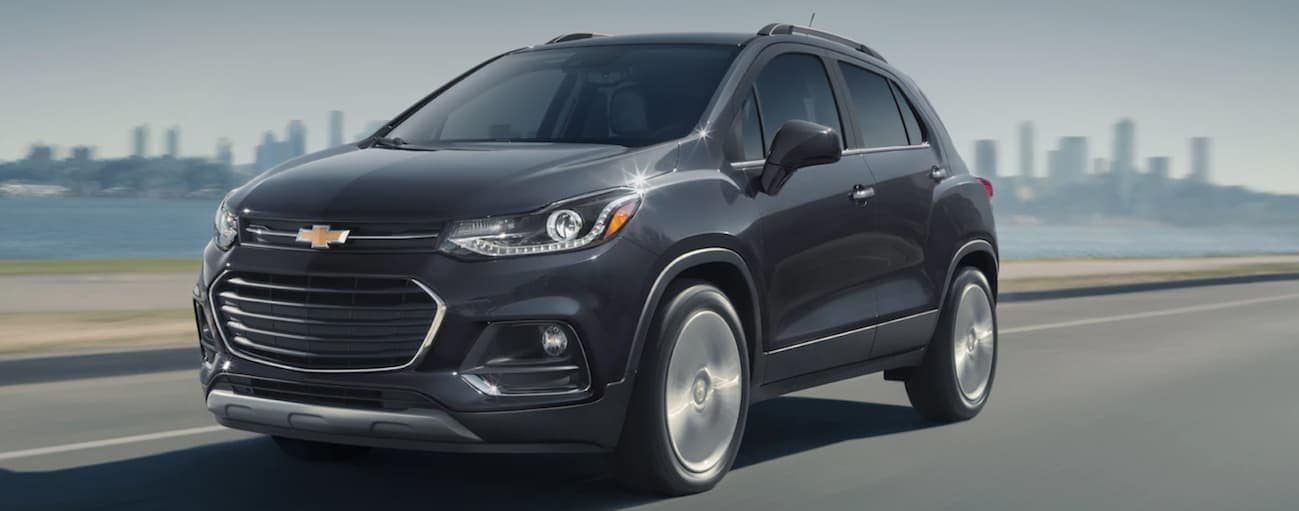 A black 2020 Chevy Trax, which wins when comparing the 2020 Chevy Trax vs 2020 Nissan Kicks, is driving on a highway with a city skyline in the distance.