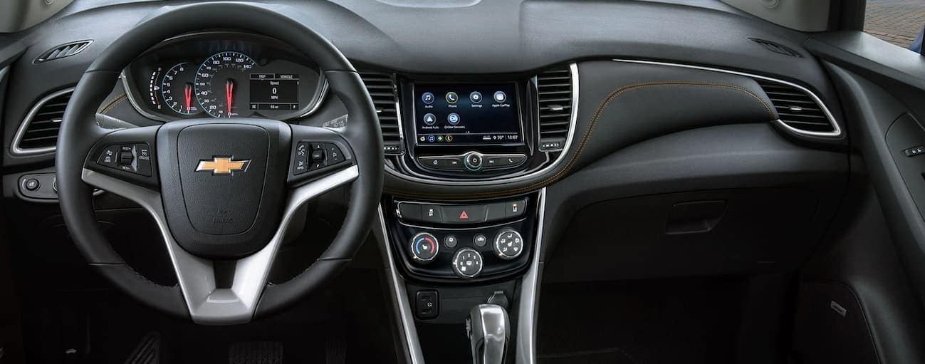 The front black interior of a 2020 Chevy Trax is shown with an infotainment system and driver's display.