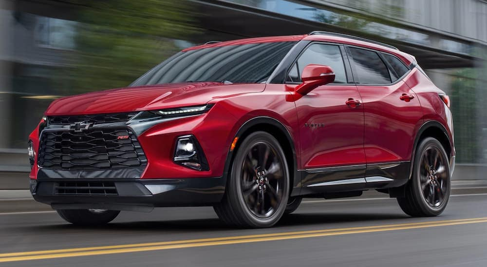 A red 2020 Chevy Blazer, which is a popular option among Chevy SUVs, is driving past blurred buildings near Albany, NY.