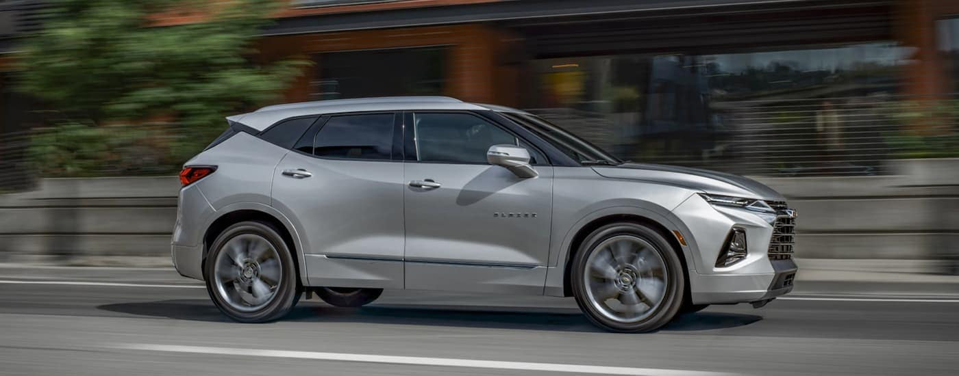 A silver 2020 Chevy Blazer is driving past brick buildings near Albany, NY.
