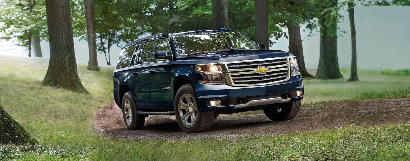 A blue 2020 Chevy Suburban is driving on a dirt trail in the woods.