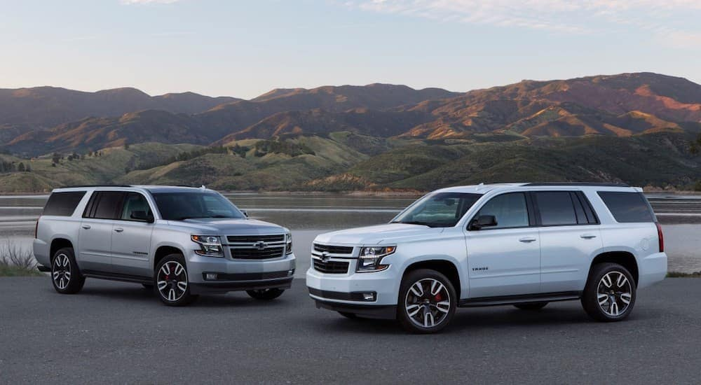 A white 2020 Chevy Tahoe is parked next to a silver 2020 Chevy Suburban, which are two popular Chevy SUVs, in front of mountains.