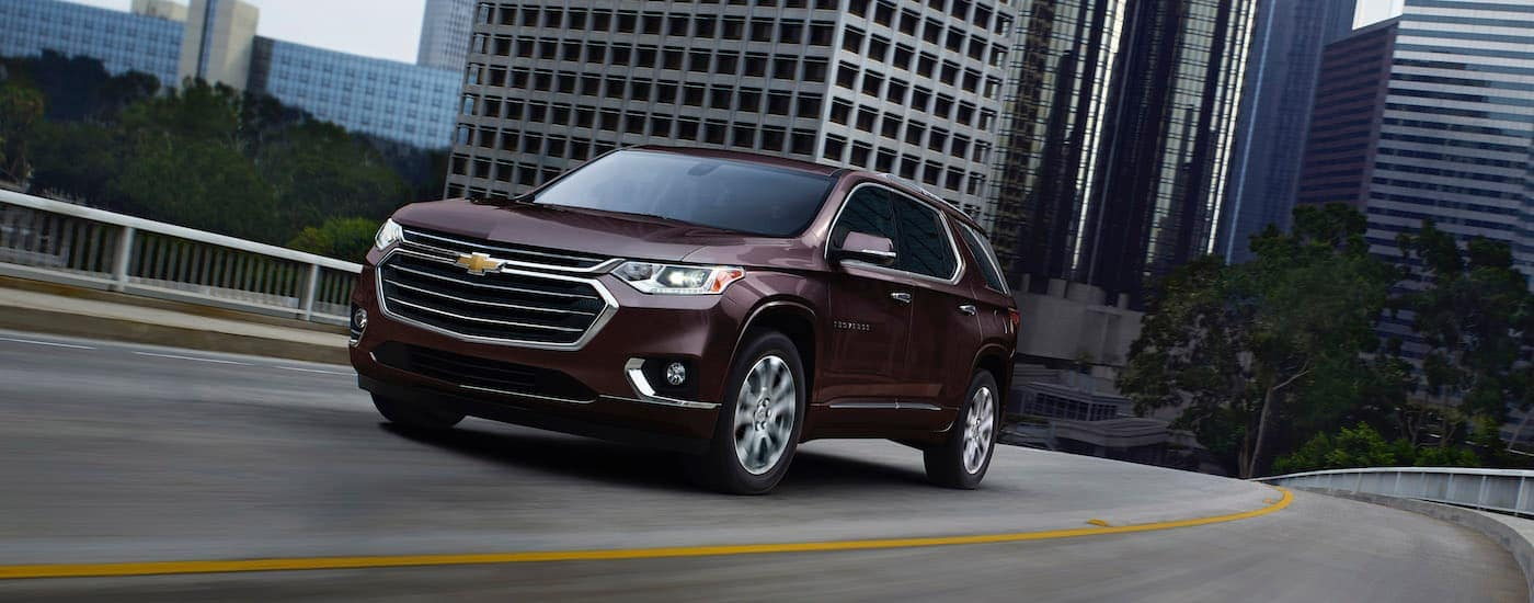 A burgundy 2020 Chevy Traverse is driving out of the city.