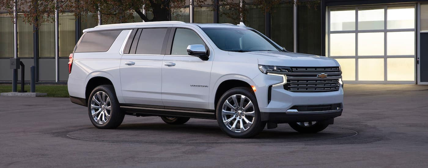 A white 2021 Chevy Suburban, the largest of the Chevy SUVs, is in front of an office building near Albany, NY.