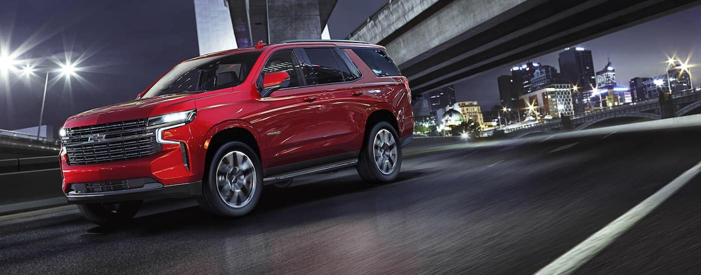A red 2021 Chevy Tahoe RST is driving past a city at night.