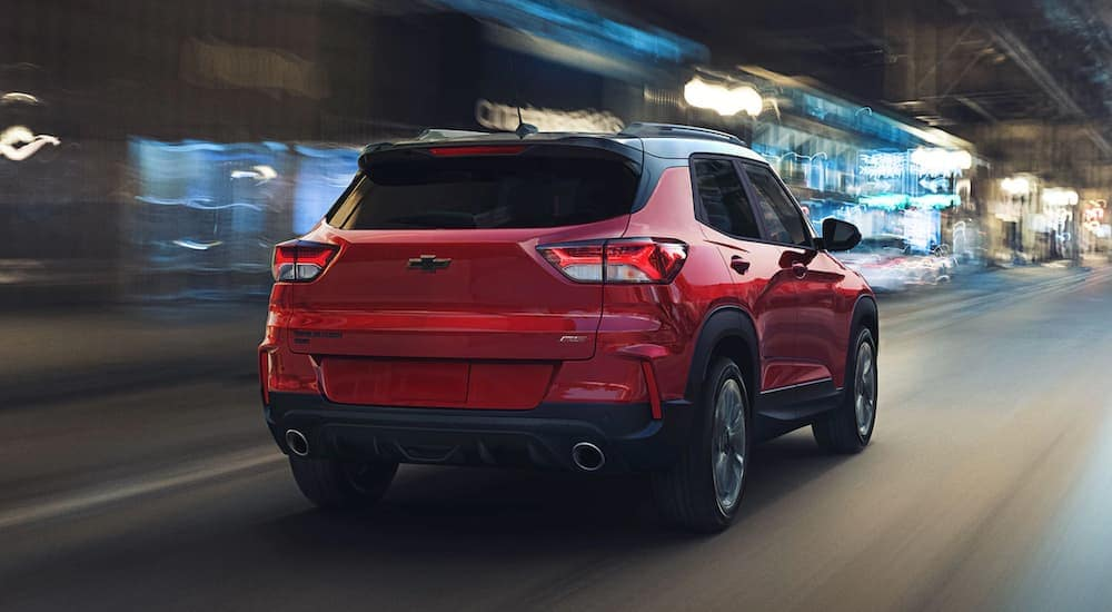 A red 2021 Chevy Trailblazer is driving on a city street at night near Albany, NY.
