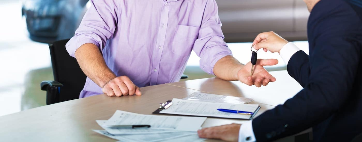 A salesman is handing keys to a customer after filling out the finance paperwork.