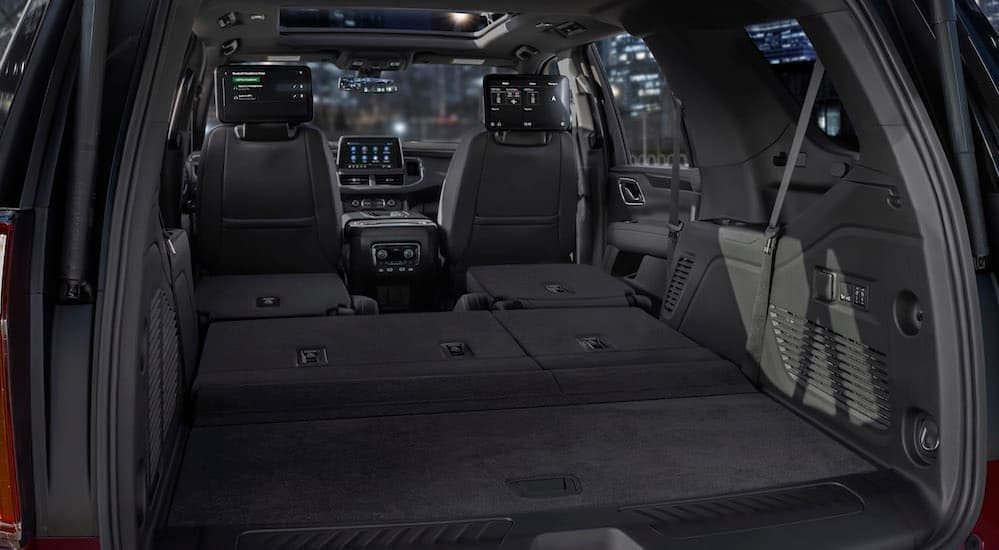 The black leather interior of a 2021 Chevy Tahoe is shown with all of the rear seats folded down.